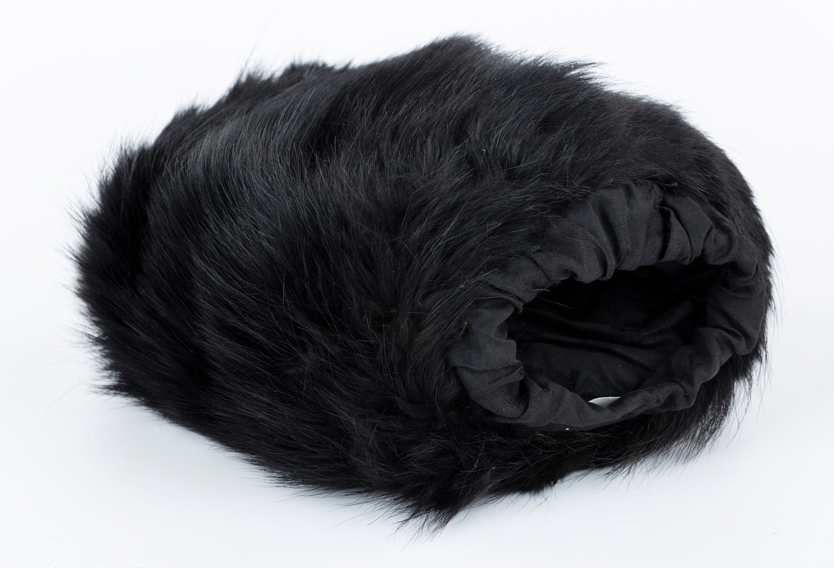Muffe i pelsskinn. Foret mes satinvevet sort stoff. Vattert mellomlegg.