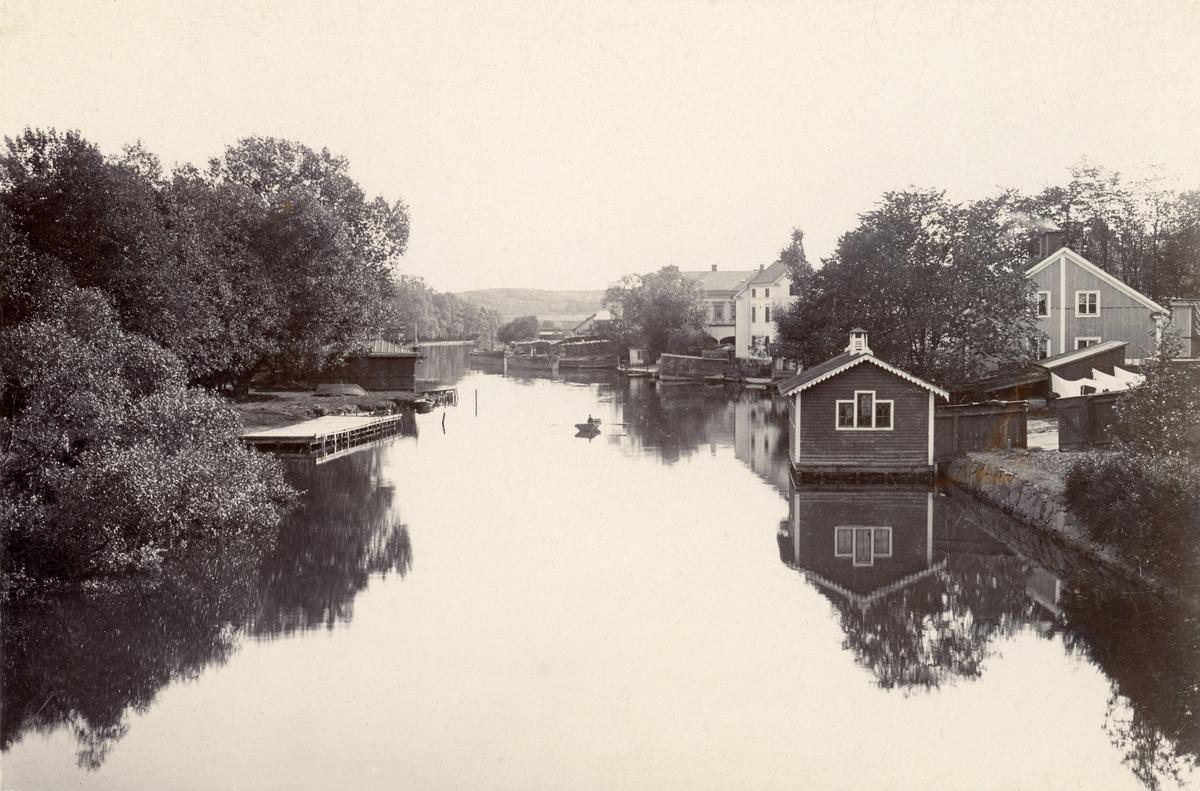 Linköpingsvy. Utblick söderut från Stångebro. Tiden är 1890-talets senare del. Till vänster i grönskan skymtar stadens Kallbadhus för herrar respektive damer. Närmast till höger ses delar av Linköpings fattighus följt av Asklundska tobaksfabriken.