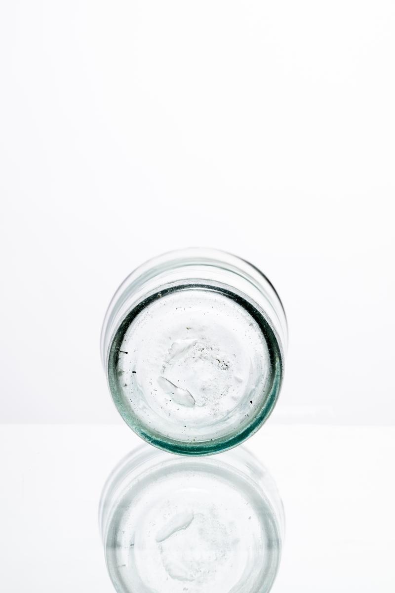 Dricksglas av klart, något grönfärgat glas. Rak modell, ojämn höjd, plan botten med puntelmärke. Skadad i mynningen. Hantverksmässigt tillverkat på Sunds glasbruk, Jönköpings län. Se vidare Historik.