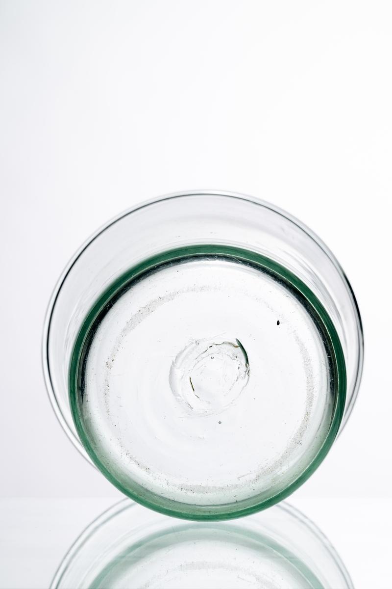 """Skål/bunke av klart, ofärgat glas. Rund, hög, smal modell med utsvängda sidor. Puntelmärke under botten. På sidan ristad märkning: """"1927 27/4"""".  Sunds glasbruk i Äng, Barkeryd socken, lades ned den 30 april 1927. Hantverksmässigt tillverkad på Sunds glasbruk, Jönköpings län. Se vidare Historik."""