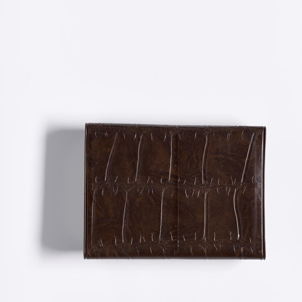 Et brunt etui i imitert skinn (krokodillle). På fronten sitter en trykknapp. Inn i etuet er det to holdere til kort.  To kortstokk i et etui av imitert skinn.