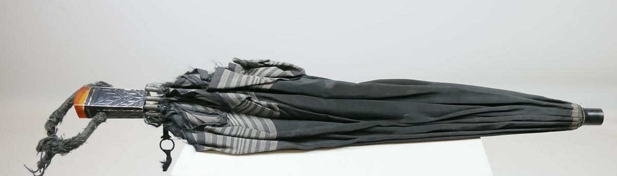 Svart paraply med tekstil og svart trehåndtak. Den nederste delen av håndtaket er firkantet med dekordetaljer og en ravfarget del. På håndtaket er det et tekstilbånd. Nederst på tekstilen på paraplyen er det grå striper Paraplyen har 15 spiler.
