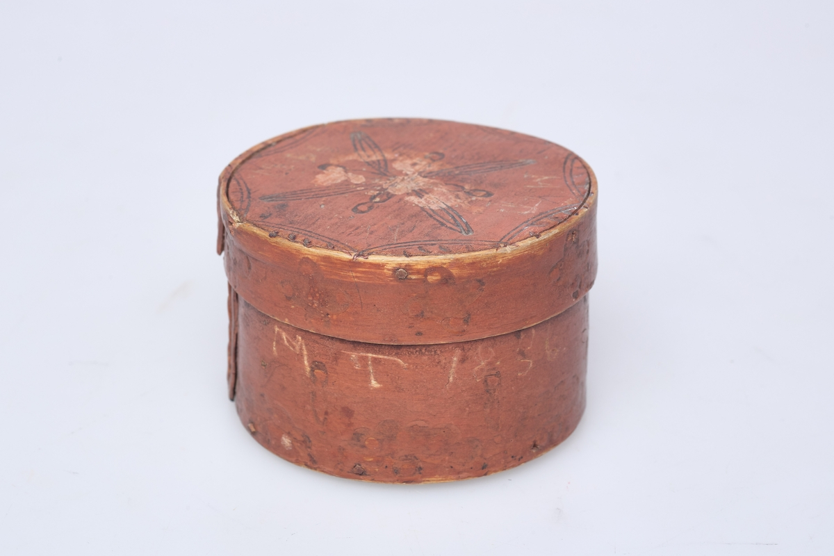 Rund brunmalt dåse av tre som er laget av tjukk høvelspon, endene, endene er sammenfestet med tæger, sviornamentikk på sider og lokk.
