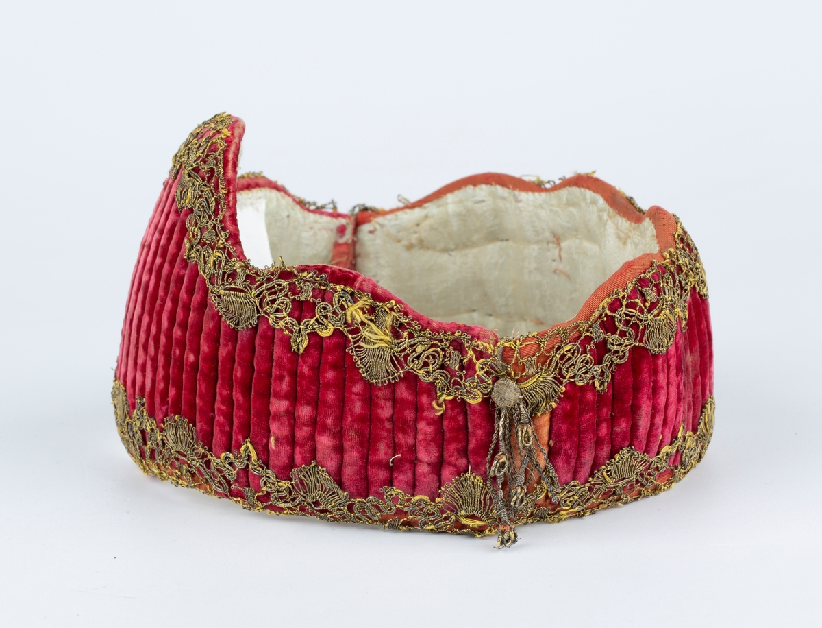 Formet som krone. Fløyelk kantet med kniplingsbånd i gulltråd. Foret med silke.