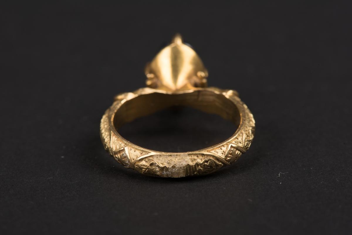 """Ring av guld med oval safir. Safiren vilar i konisk fattning med fyra gripklor. Ursprungligen var troligen ringen belagd med emalj. Ringens utsida har bokstavsfält med betydelsen """"safiren vakar över Eden""""."""