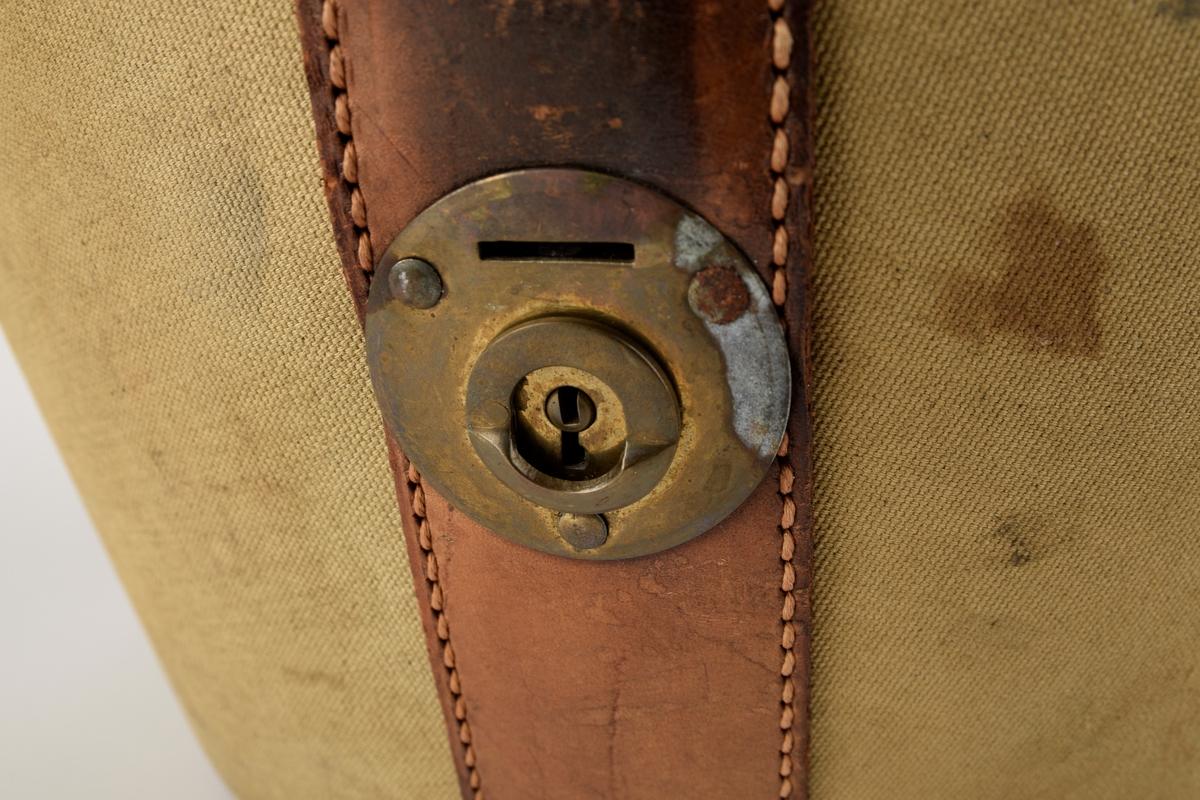 Hatteeske til flosshatt.   Oval grunnflate. Sidene på esken skrår utover. Buet lokk. Reimer og kanter av skinn. Lokket er hengslet med skinnreim. Reimen går over lokket og ender i lås i front. Bærehåndtak av skinn på lokket, der endene har metallhemper for festing av reimer fra eskekroppen. Innvendig kledd med grå, mønstret tekstil. To reimer med trykknapp går på tvers av esken innvendig.