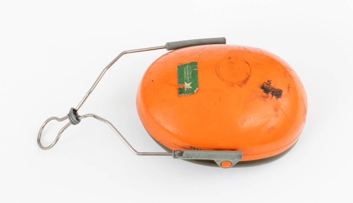Hørselvern, øreklokke, av typen Peltor H9. Hørselvernet, øreklokka, består av en ovalt formet halvkule av støpt plast med innlegg av skomgummi og en væskefylt tetningsring som omslutter brukerens øre. Innleggene og tetningsringene er utskiftbare. Det er festet en metallbøyle  med glidefeste for høyderegulering til øreklokka. Øreklokkas metallbøyle monteres på hjelmfestet. Det er surret en ståltråd rundt metallbøylen.