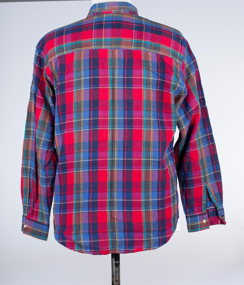 Skjorte. Krage med linning. Bærestykke dobbelt. 2 brystlommer med klaff. Forknappet, 7 knapper og knapphull. Skjorten merket Erland Johansen. Han var bror av Erland Johansen.