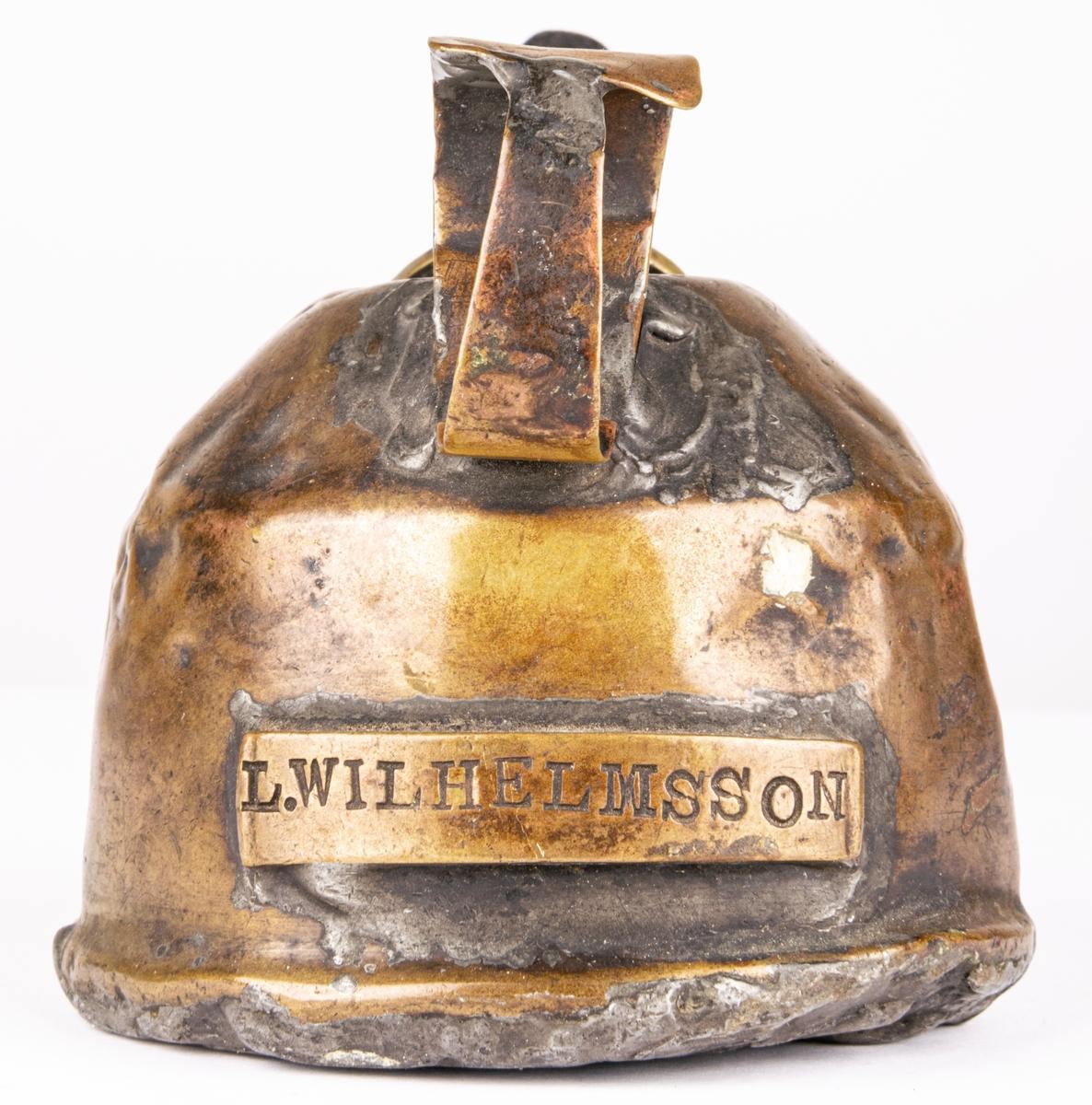 Kat. kort: Rovoljelampa, av mässing. Användes för att lysa sig med vid smörjning av lok. Ägare L. Wilhelmsson enl. påsvetsad namnskylt. Lampan lagad med tenn i botten. Pip på 4 cm sticker ut från kannan. Pipen, som nertill slutar i en cirkelrund platta, är avskruvbar genom gängor i och för påfyllning av rovolja. Handtaget på lampan är, där det är som bredast, märkt. Lampans höjd, utom pip och handtag, 6,5 cm, omkretsen vid botten 27,2 cm. Har tillhört GDJ.