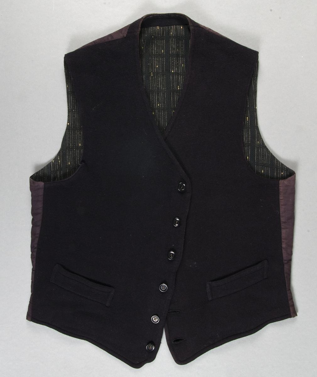 Väst av svart vadmal. Sex knappar. Två fickor. Spänntamp i ryggen. Bakstycke av svart bomullslärft. Foder av mönstervävt ylletyg i svart och vitt.
