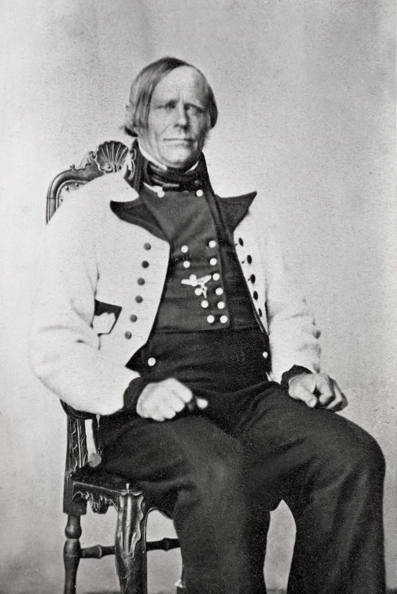 Augund H. Eika sitjande i gråkufte i fotoatelier