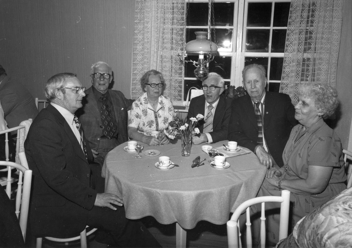 Två kvinnor och fyra män sitter runt ett bord och dricker kaffe med avec.