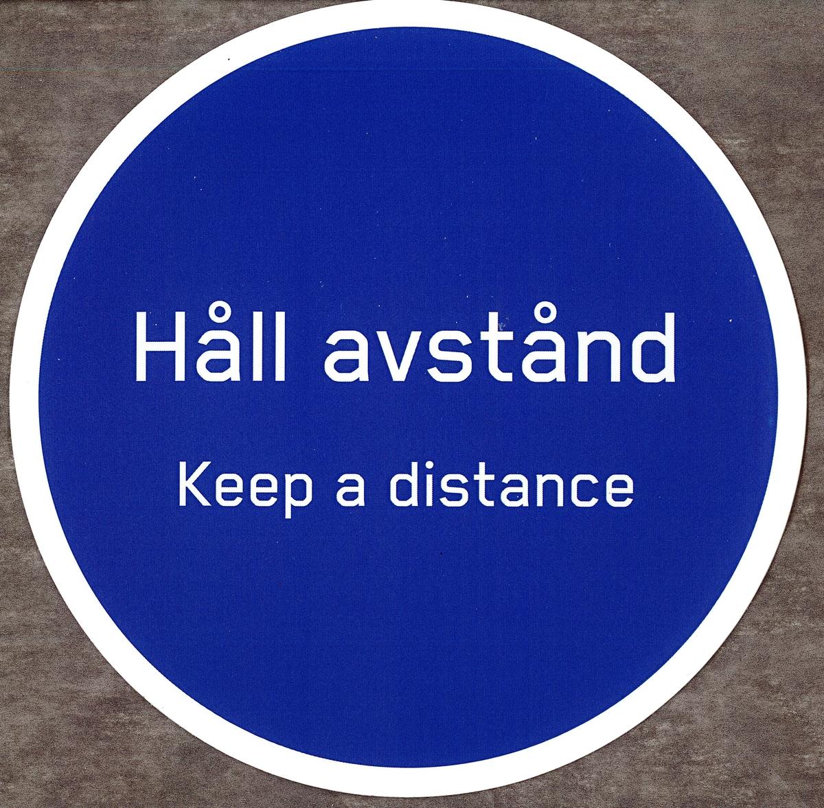 """Blå rund klisterdekal med texten """"Håll avstånd Keep a distance"""" i vitt. Vit kant runt om. Vit baksida."""