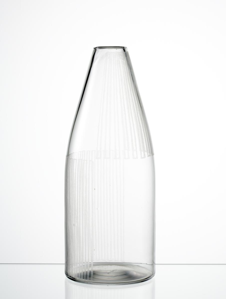 Vas, cylindrisk, med konande hals mot mynningen. Graverade spegelvända ränder på hals och buk.