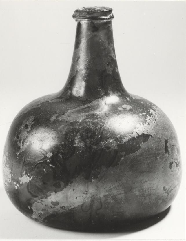 Bukig flaska med grönt glas, antydan till axlar. Troligen tidigt 1700-tal.