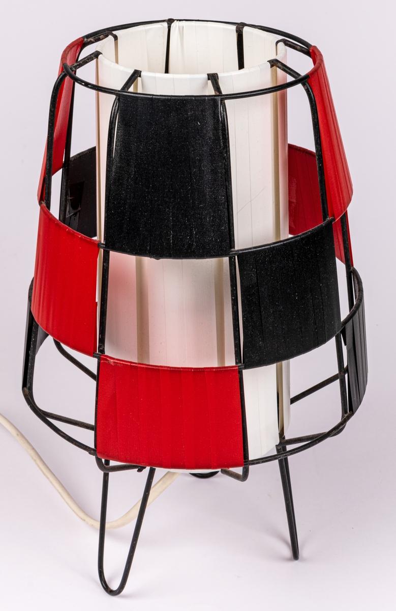 Bordslampa, svart plastklädd metallställning. Plastremsor trädda i rutmönster i svart, rött och vitt.  Raketformad.