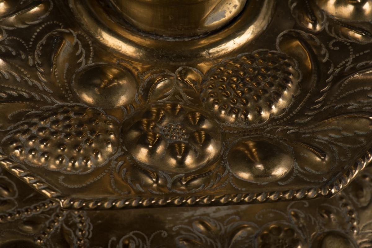 Ljusstake med vridet skaft och löstagbar ljushållare av mässing. Basen är åttkantig, liksom ljushållaren och underdelen till skaftet. Dessa delar liksom den runda foten är rikt dekorerat med driven och punsad dekor i form av bucklor och stiliserade vegetativa ornament.