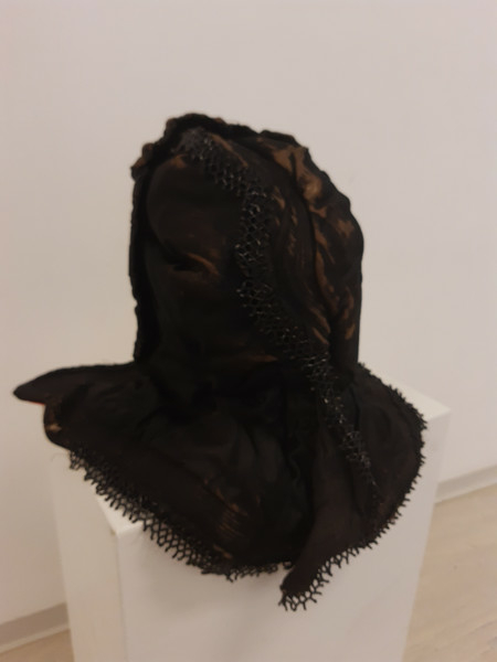 Kyse av sort silke, pyntet med dobbel rysjkant foran, og med avlange perler som danner en bord midt over og rundt kanten. Innenfor perlekanten er det sydd en bord med stikninger. Kysen er foret med rødt bomullsstoff.