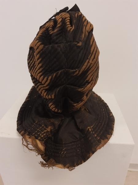 Svart, foret kyse, med rosett av bånd i samme stoff som kysen.  Den er vattert, og foret er av sort vasketøy.