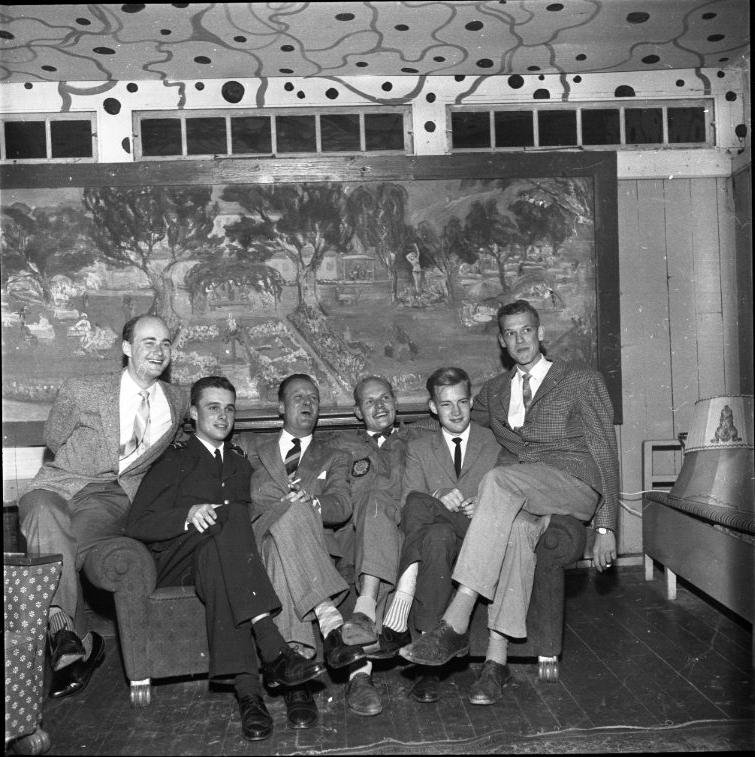 """Sex herrar sitter i en soffa. På väggen bakom dem hänger Karin Stacklebergs målning """"Ribbagårdens trädgård"""", daterad 1935."""