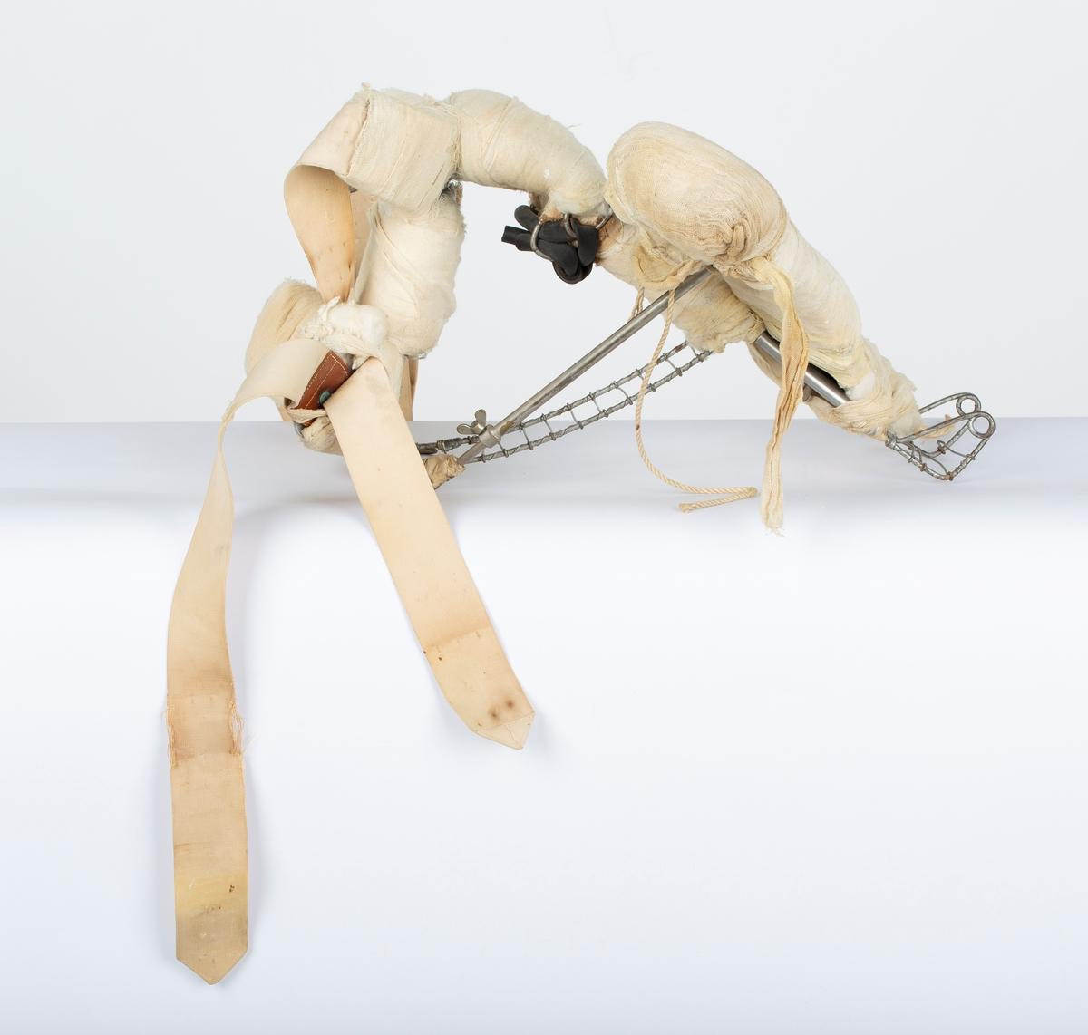 Støtteskinne for brukket/skadet arm. Bøyler mot overkropp, regulerbar. Vattpolstring, surret med gasbind.