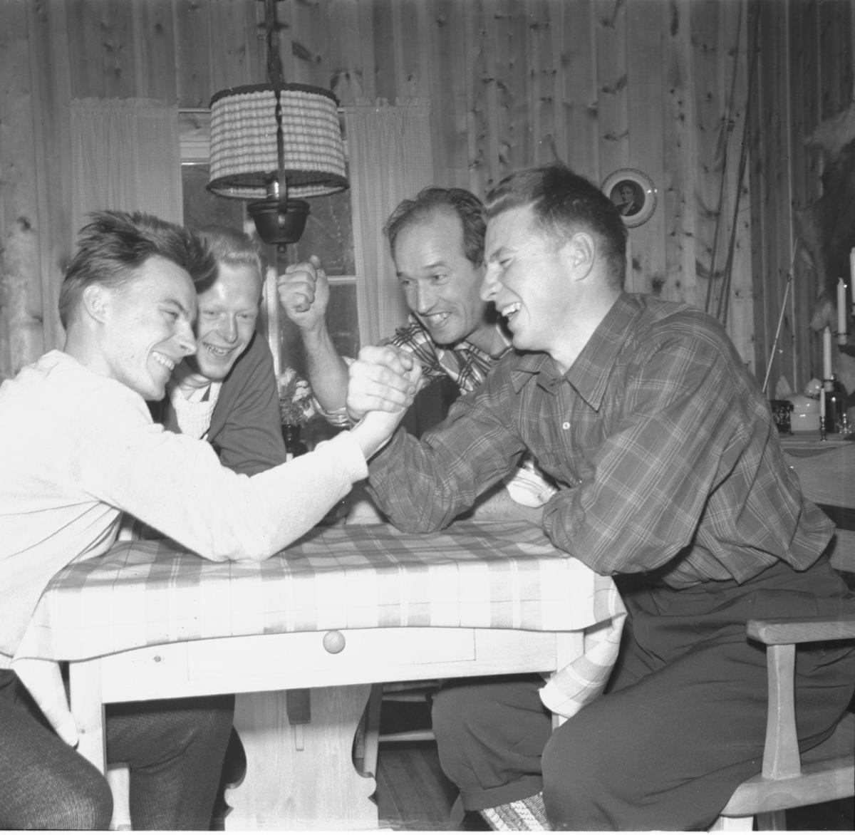 To menn bryter håndbak, mens to heier. Lampe, Bilde