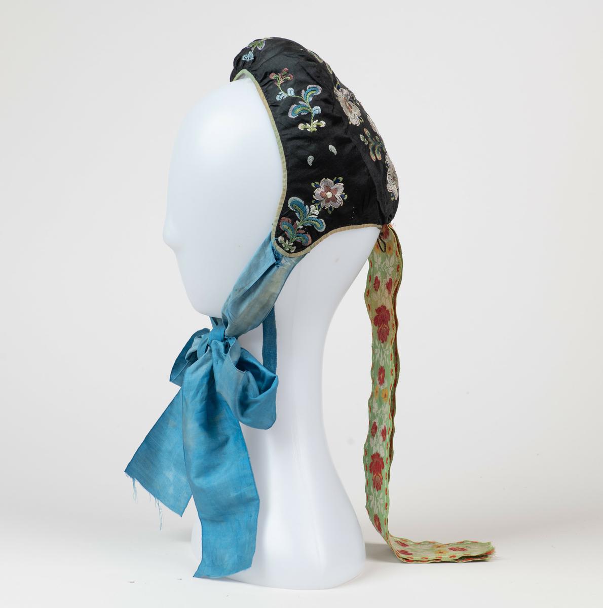 Lue. Kvinnelue, sydd av sort silke. Brodert med blomster i silkegarn på for- og bakstykket. Kantet med et smalt bånd av grønn silke. Knytebånd under haken av blå silke, og nakkebånd av vevd, blomstret silke. Foret med tynn, mønstret bomull.