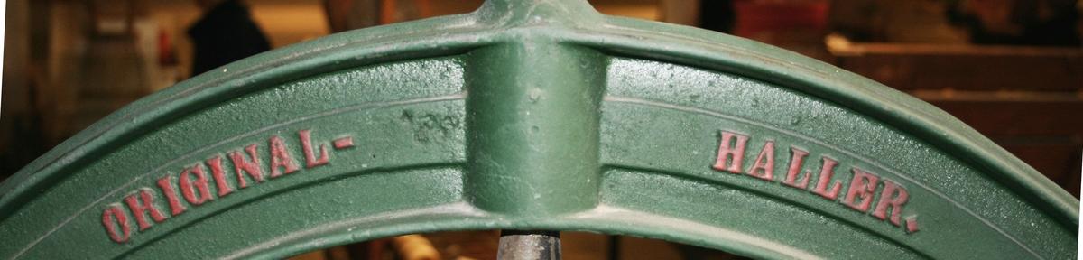 Mangel av trä, på grönt järnstativ. Två över varandra liggande trävalsar, som erhålla tryck, genom bladfjäder, vars spänning, regleras från upptill befintlig järnbåge med vingskruv. Balanshjul med handtag, för manuell drift. Med kugghjulsutväxling. Märkt: ORIGINAL HALLER. Proveniens Sandbloms Linneväveri, Funningen.