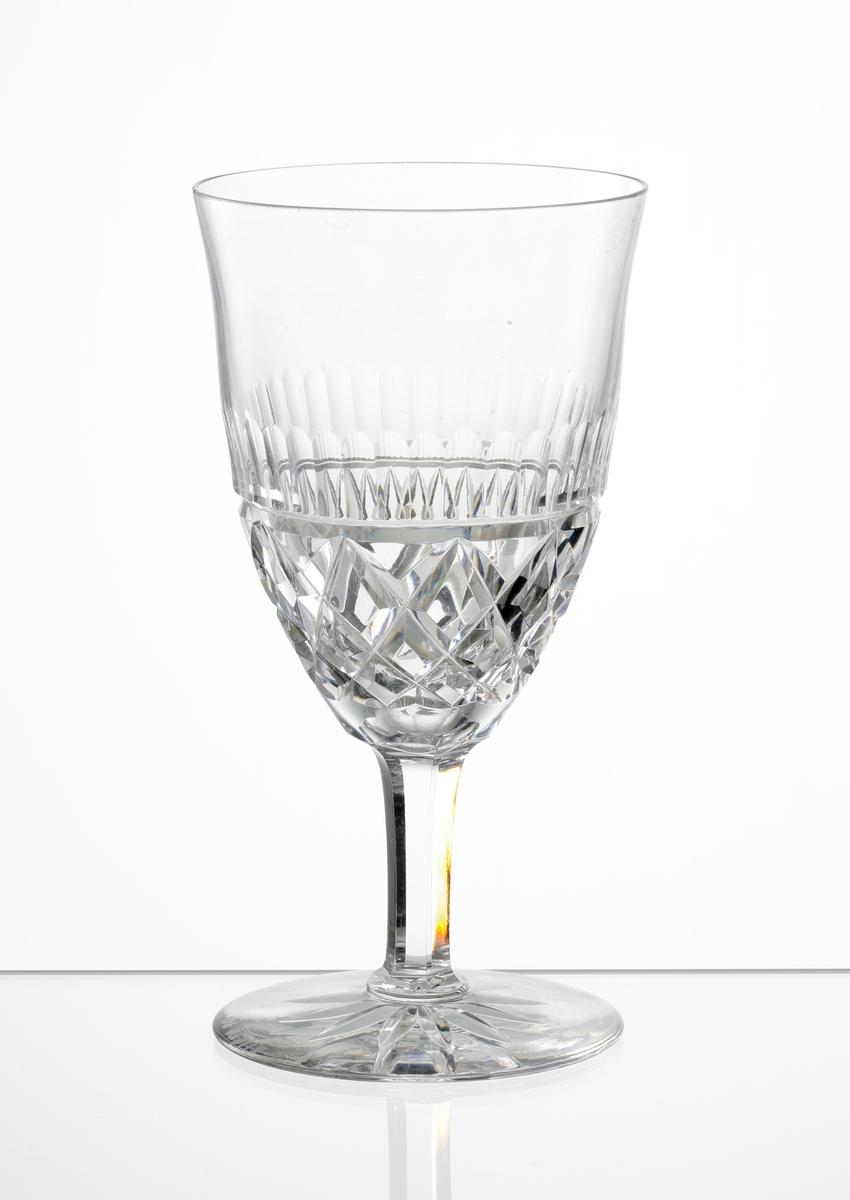 Rödvinsglas med lätt klockformad kupa, skärslipad nedre del med olivslipad bård. Fasettslipat ben. Fot med skärslipad stjärna i botten.