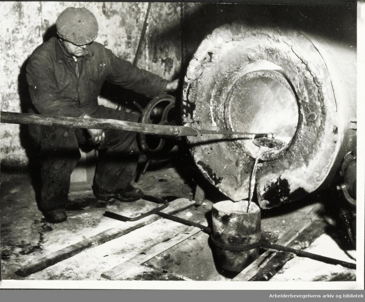 """Kongsberg sølvverket."""" Olaf Lurås sørger for å tømme den store digel ovnen for de siste dråper sølvmasse"""""""