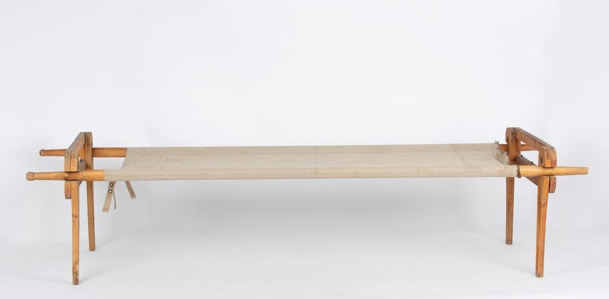 Rektangulært bærestykke av seilduk, langsgående lomme på hver side. Stropper og maljer på ene kortsiden.  Bærestenger av løvtre. Det følger med 2 sett sengebein.