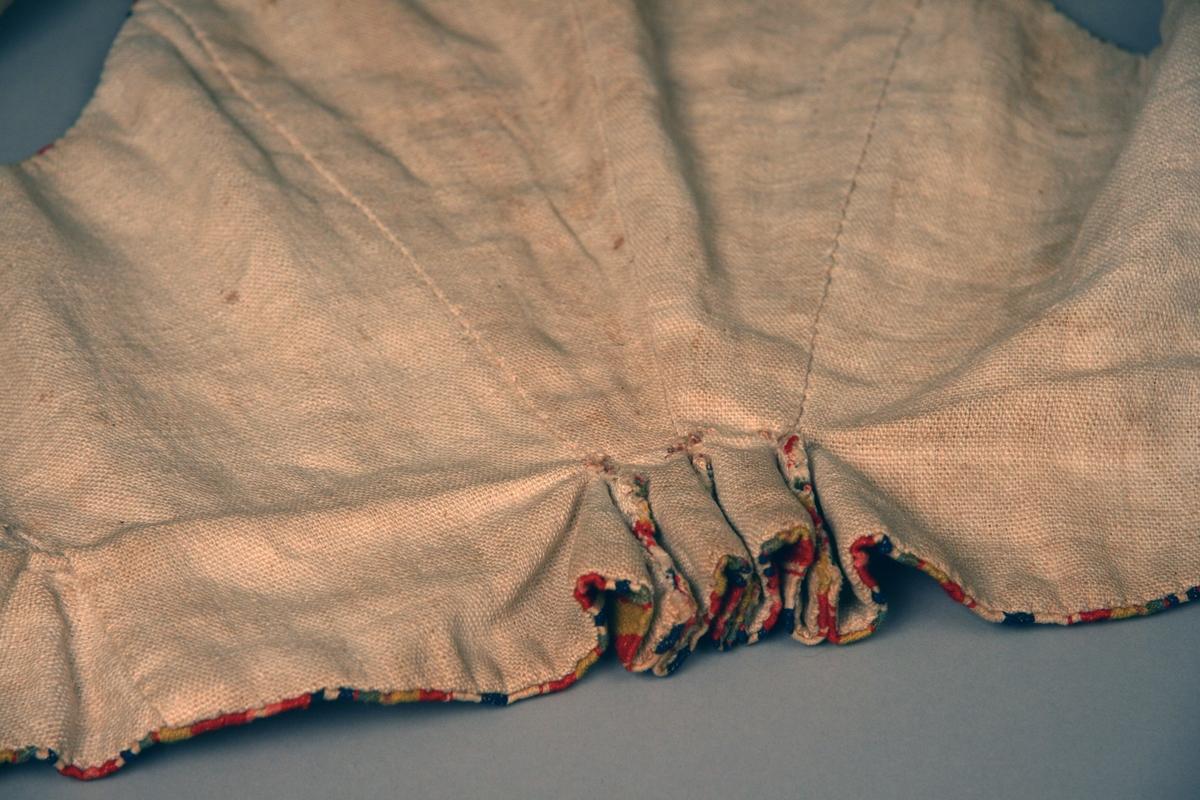 Livstycke av randigt ylletyg i rött, rosa, blått, vitt, grönt och gult. Insidan är fodrad med beige linnetyg. I nederkanten isydda kilar i sidorna, baktill är livstycket veckat,  framtill går kilarna omlott när livstycket knäpps med fem hyskor och hakar.