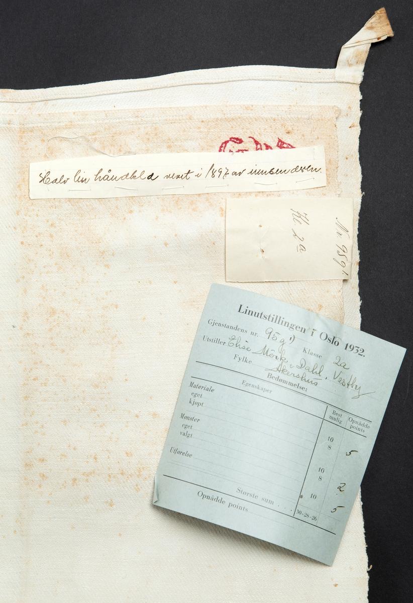 """Håndkle, håndvevet i 1897. Hempe i 2 hjørner. Monogram EM sydd med rød tråd Merket: """"Linutstillingen i Oslo 1932. Gjenstandens nr. 95 g´1. Klasse 2a. Utstiller: Elise Mørk, Dahl, Vestby. Fylke: Akershus. Bedømmelse: Materiale 5, Mønster 2, Utførelse 5. Håndskrevet lapp sydd fast: """"halv lin håndklæ vevet i 1897 av innsenderen""""  Tilvirket av Elise Mørk i 1897 Gitt av Marit Linnestad Eiet av Tordis Mørk Pettersen Kjøpt på auksjon Dal gård, Erikstadbygda, Vestby"""