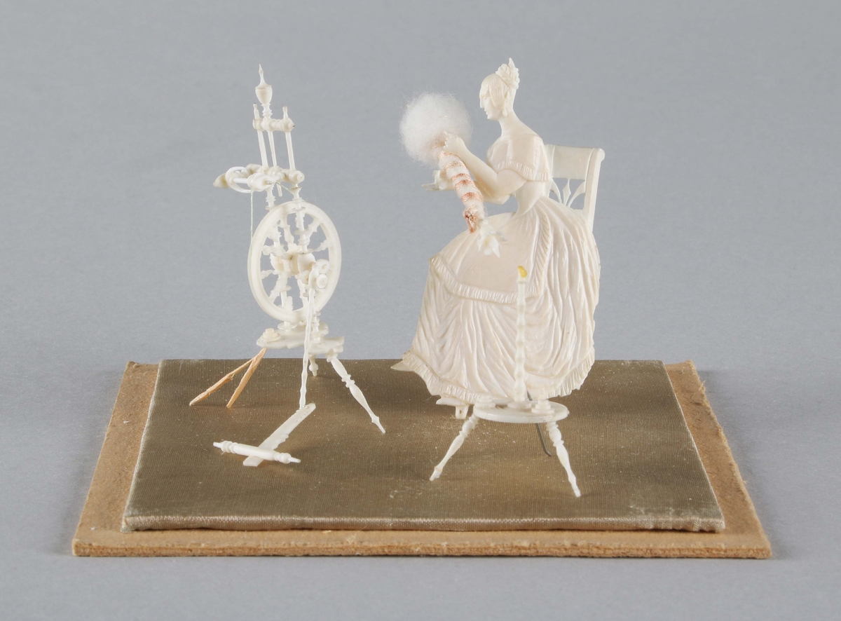 Figurgrupp i snidat elfenben. Sittande kvinna med spinnrock och garnvinda. Spinnrocken och garnvindan står på tre fötter. Båda saknar en fot. Står på sidenklädd tunn platta, som i sin tur är limmad på bottenplatta av papp. Förvaras under fyrsidig, kvadratisk glasmonter. Mått: 90x90 mm.  Funktion: Prydnadsföremål