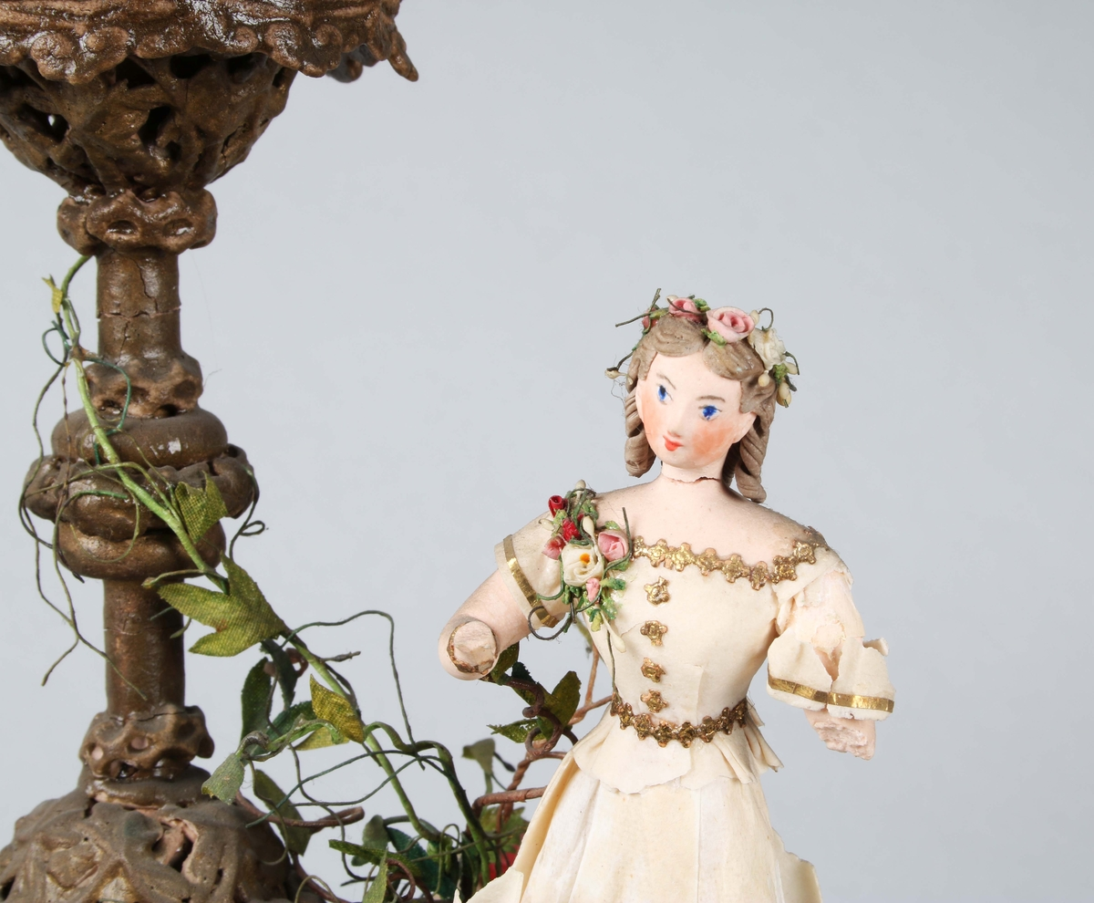Dragantarbete. Figurgrupp. De 4 årstiderna. 4 flickor som symboliserar årstiderna, i form av vinter, vår, sommar och höst. De sitter och står, runt, centralt placerad hög vas, med rosor upptill. Förvaras under fyrsidig, rektangulär glasmonter. En hand och en underarm saknas. Åldersslitage.  Tillverkad av Hilda Boström (1822-1903), sockerbagare, Borås.  Litt: Se Årsbok 1963, sidan 46. Litt: Se Ada Damms Boråsbilder.  Funktion: Prydnadsfigurin