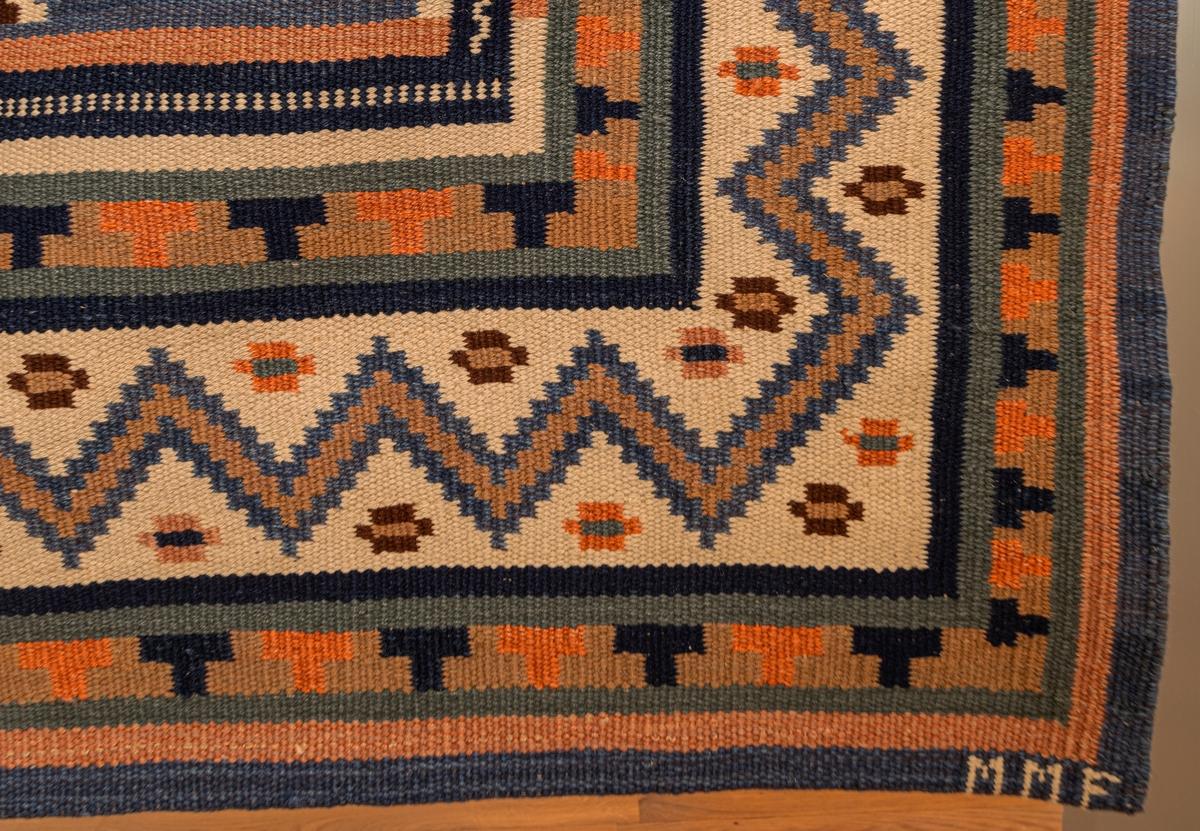"""Matta 301 x 232 cm. """"Nio stjärnor"""". Röllakan. Varp av lingarn Inslag av ullgarn. Blå botten med nio riddarstjärnor i flera färger. rik bård med T-ränder och zigzagrand. Sign. MMF Köpt omkring 1910 för Gustaf Bergströms gästrum på Hofors, ärvd av H.U. vid dennes död. Märta Måås-Fjetterström."""