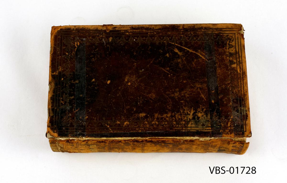 Slitt tykk Bibel. Innbundet i preget lær.   Dekorasjon trykt inn i begge to skinnpermen. Ordet Bibelen er trykt med gullbokstaver (bladgull) på kanten.  Bibelen er trykt med gotiske bokstaver.