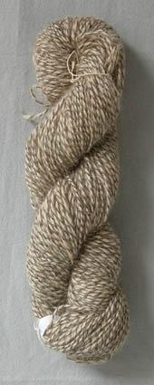 Härva med 3-trådigt hundhårsgarn, handspunnet av lantrasull och hundhår. 2 trådar vit och en tråd mörkgrå är tvinnad ihop. Härvan har 90 trådar och är 1900 mm i omkrets.