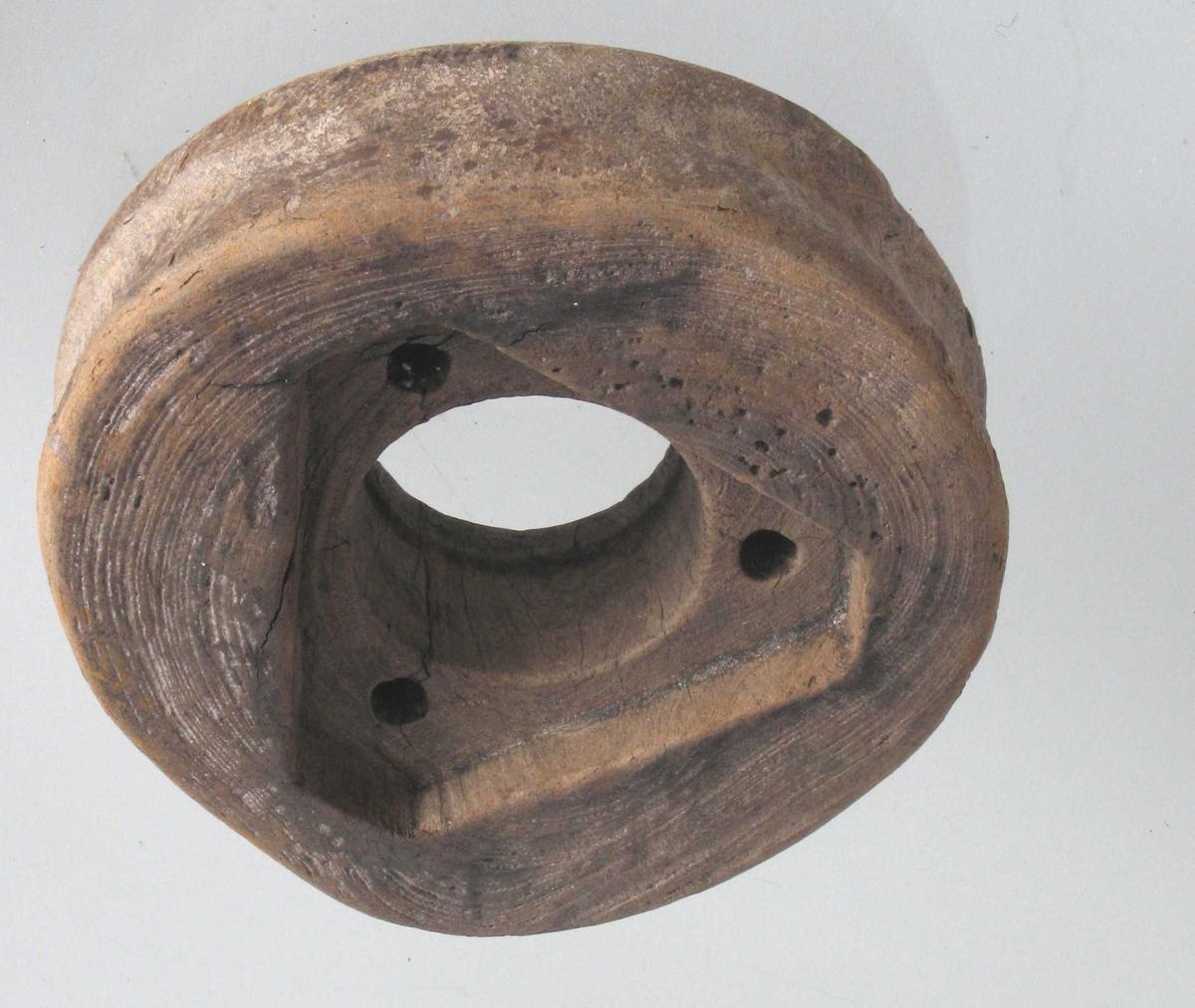 Pukkenholt. Ktaftig, glattskurt blokkhjul med tre boltehull  på den ene side, på den annen en trekantet  innskjæring for jernbeslag (boltehull=naglehull; jernbeslag= bøssing; krg anm.)