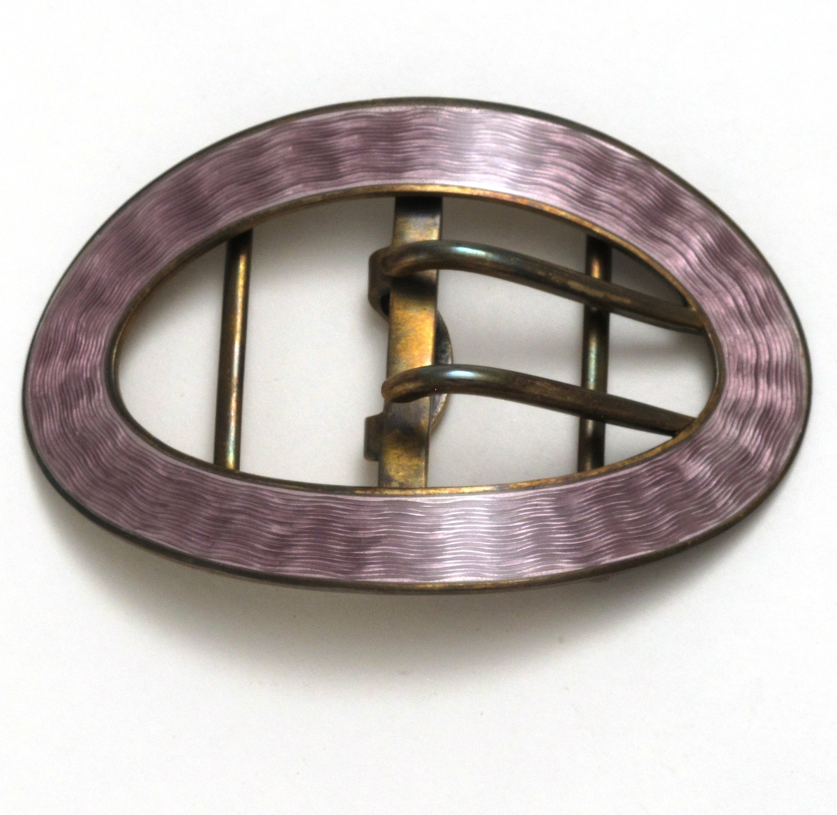 """Spenne og knappesett i etui   Sterlingsølv og emalje.  Stpl.  J. TOSTRUP 925 S.  a) Oval beltespenne med bleklilla emalje over guilochinert sølv, baks. forgylt, L. 7,8 Br. 5,3 cm.  b) Spissoval spenne (nål)L. 4,5 Br. 2, bleklilla etc.  c,d,e,e,f,g,h)    6 kvadratiske bluseknapper, 1x1, cm, bleklilla emalje over """"løpende hund""""' i sølv. Ustemplet.  i) Hvitt skinntrukket  etui, Innv silke og fløyel, stpl.  J. TOSTRUP: KRISTIANIA  Tilst. 1994: Helt ubrukt."""