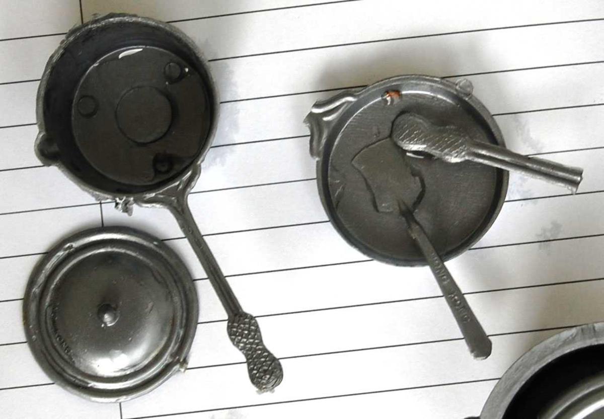 """Dukkekjøkkenstell i sølvgrå plast. Grovt sprøytestøparbeid med grader og produksjonsmerker. Noen hanker har fått en dråpe svart for å markere bakelitt. Settet består av et """"gassbluss"""" på trefot, 1 stor og 2 små kjeler med lokk, 1 stor og 1 liten kasserolle med lokk, 1 stekepanne (hanken er knekt, men ikke tapt), 1 stekespade, 1 kaffekjel med lokk (tuten er ødelagt), 1 tekjele med lokk støpt i ett stykke."""