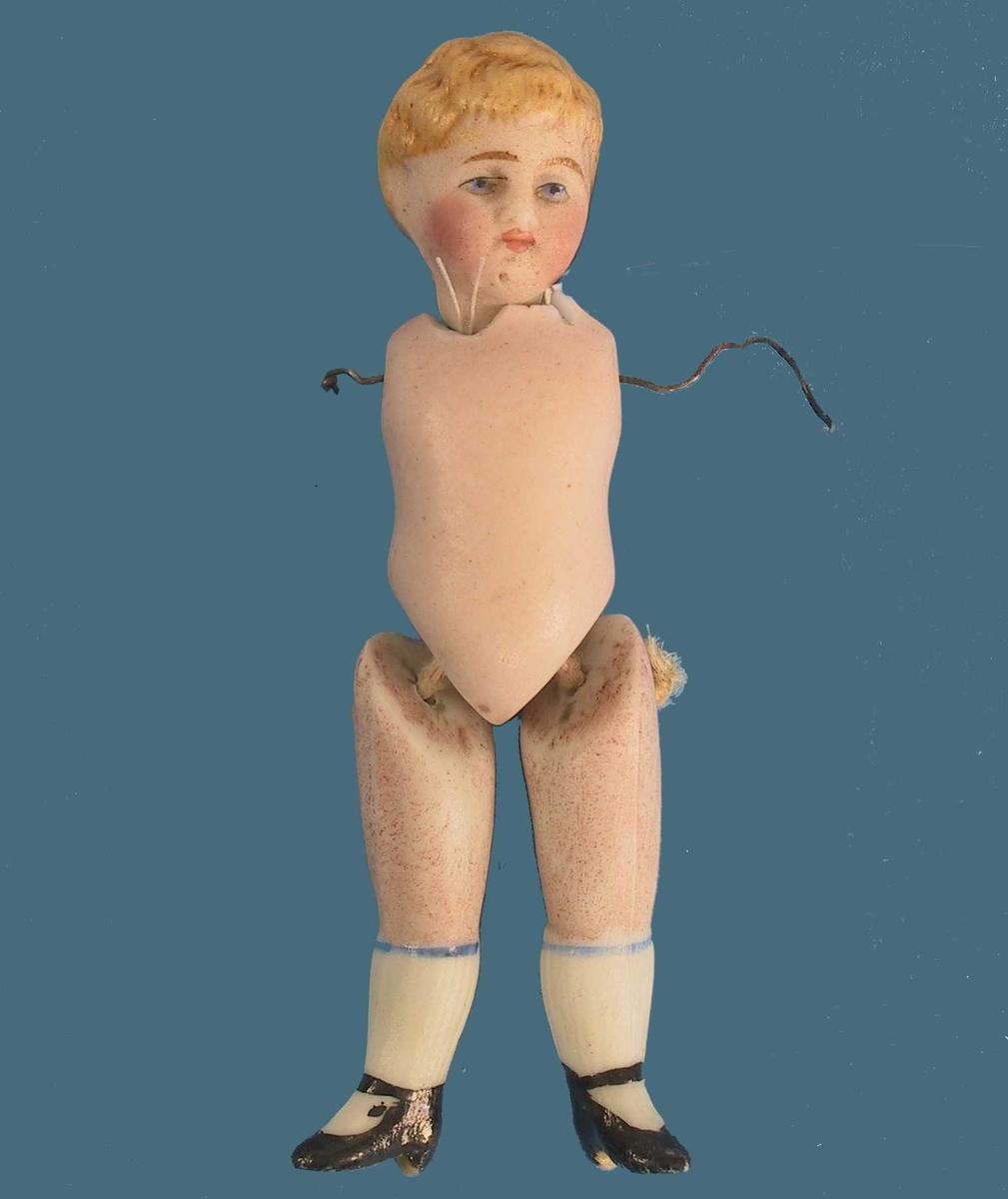 Form: Hode festet til kropp med ståltråd, armer mangler. Ben festet til krop med ulltråd.