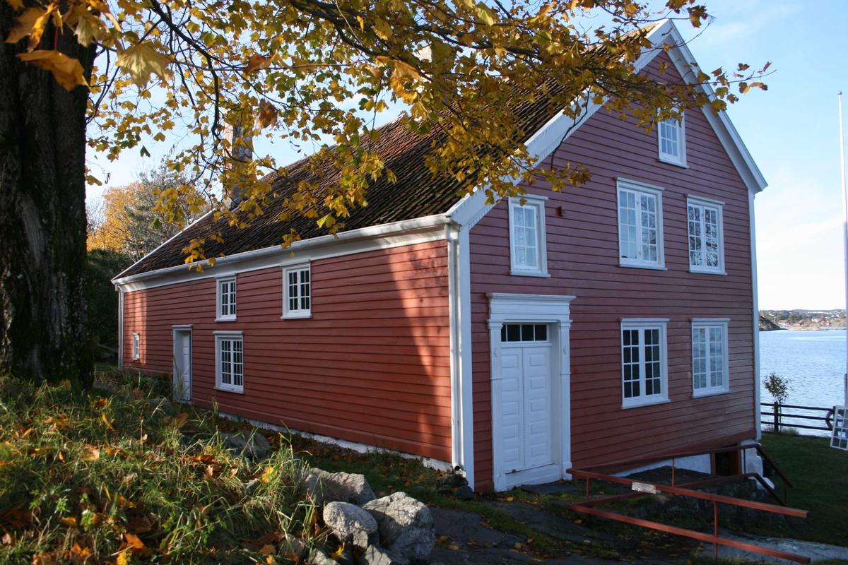 Merdøgaard, gavlvegg mot øst og langvegg mot sør, oktober 2009. Stammen på tuntreen t.v. Revesandsfjorden t.h.