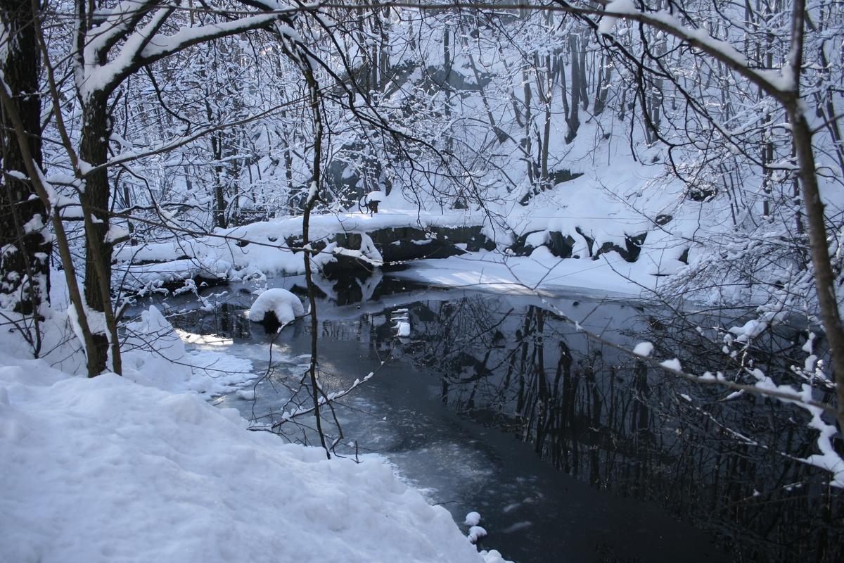 Langsæ mølledam og møllestem. Åpent vann, ellers er landskapet dekket av snø.