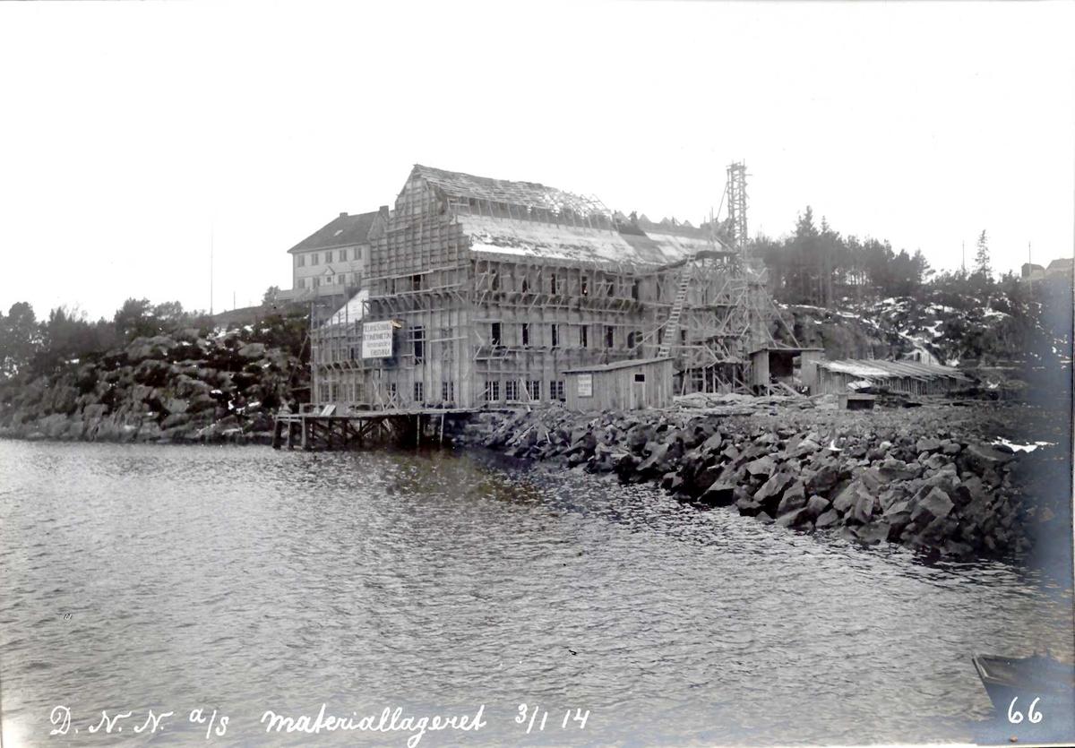 """""""03/01-1914"""" Nitriden. Bygning for materiallager, verksteder og kontorer. Heisanordning for betong. Bak Smelteverkets første direktørbolig, senere eid av Nitriden. Smelteverket bakenfor. Til høyre Nitridens fabrikktomt og høydebasseng for trykkvann. Tromøysund i forkant."""