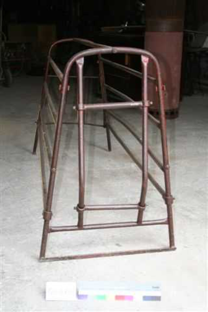Metallramme av runde jernrør. Hver av langveggene består av fire rør. Endeveggene kan åpnes.