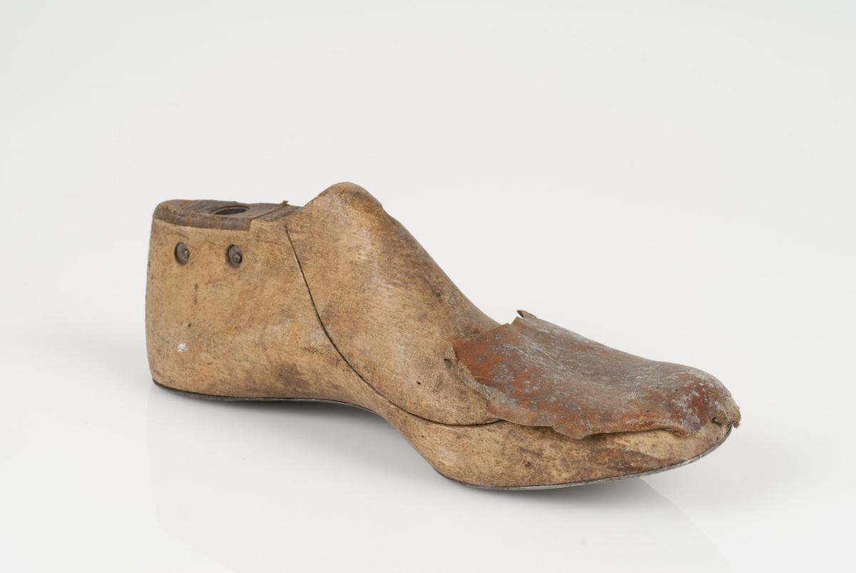 En tremodell i to deler; lest og opplest/overlest (kile). Venstrefot i skostørrelse 31, og 8 cm i vidde. Lestekam av skinn. Såle av metall. Lærhusk på lesten.
