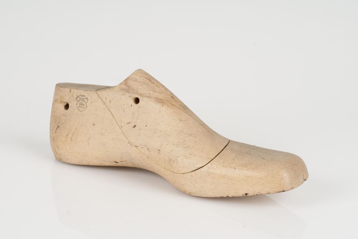 En tremodell i to deler; lest og opplest/overlest (kile) med påført tekst. Venstrefot i skostørrelse 45, og 9 cm i vidde.