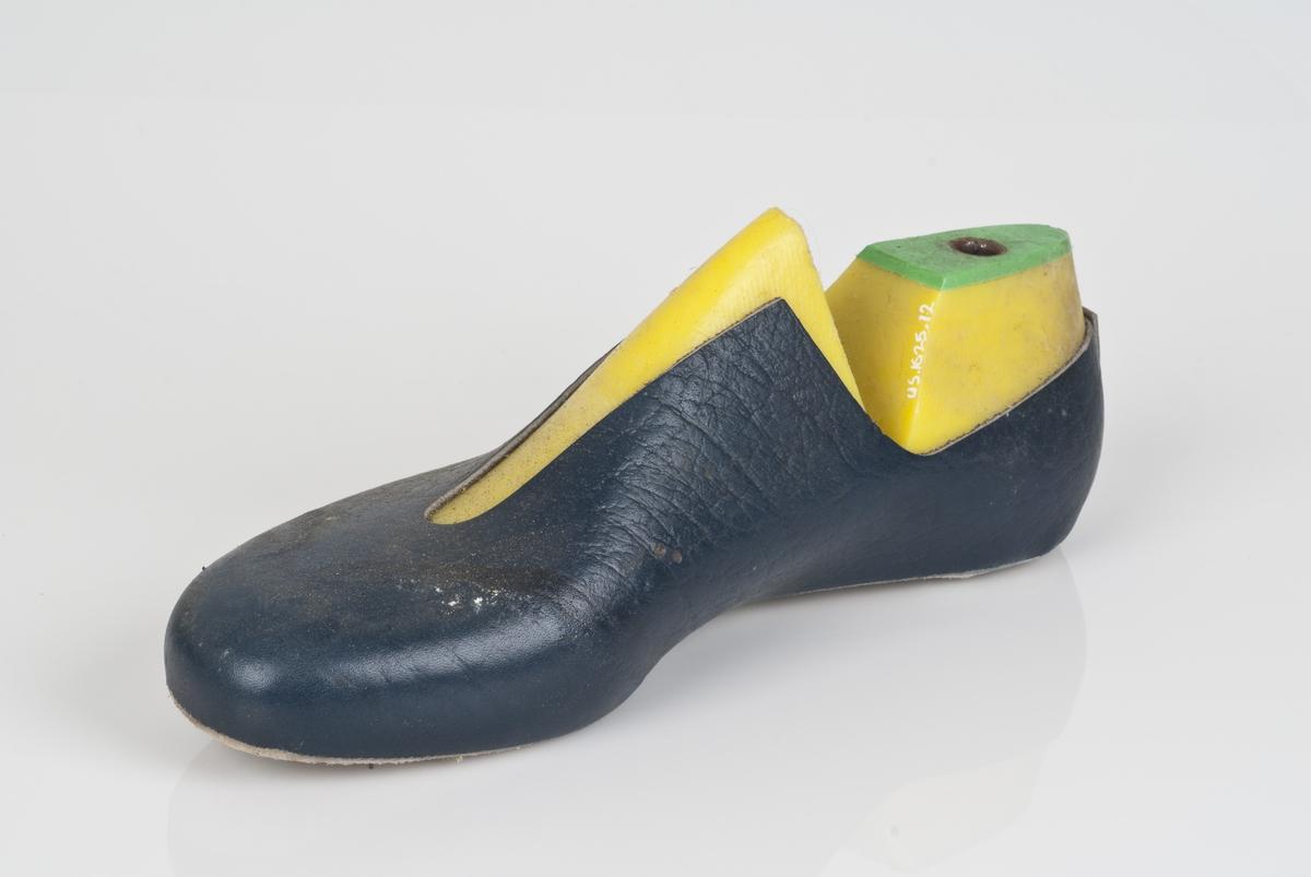 En plastlest med overlæret til støvel (fabrikkstøvel). Plastlesten er i fargen gul. Høyrefot i skostørrelse 44, med 7,5 cm i vidde. Skinntrekket er i blåfarge. Lestekam av plast i grønnfarge.
