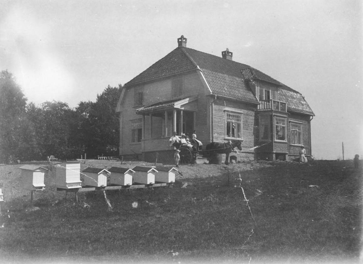 Et hus med bikuber og folk.